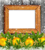 Old frame with gold christmas decoration baubles and pine on a snowbound wooden background — Stock Photo