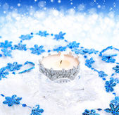 Christmas candle with blue snowflakes on a festive background — Photo
