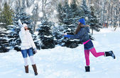 Two girls in winter throw oneself snow — Stock Photo