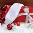 Stock Photo: SantClaus hat with christmas gift and decorations on snow