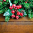 Fir twigs decorated with berries on wooden background — 图库照片