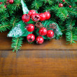 Fir twigs decorated with berries on wooden background — Zdjęcie stockowe