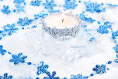 Christmas candle with blue snowflakes in the snow — Stock Photo