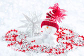 Snowman with Christmas decorations on snow — Stock Photo