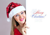 Beautiful christmas woman in Santa Claus hat with signboard — Stock Photo