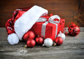Santa Claus hat with christmas gift and decorations on wooden background — ストック写真