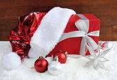 Santa Claus hat with christmas gift and decorations on snow — Stock Photo
