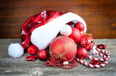 Santa Claus hat with christmas decorations on wooden background — Stock Photo