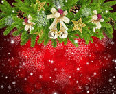 Christmas composition is with the branches of spruce and by decorations on festive red background — Stock Photo