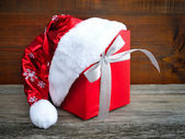 Santa Claus hat with red christmas gift on wooden background — Foto de Stock