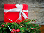 Red gift and fir twigs on wooden background — Stock Photo