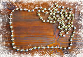 Christmas frame with gold beads on a snowbound old wooden backgr — Stock Photo