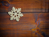 Gold decoration snowflake on a wooden background — Stock fotografie