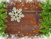 Snowbound branches of spruce and snowflake are on an wooden back — Stock Photo