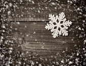 Snowflake on a snowbound old wooden background — Stock Photo