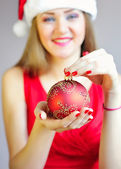 Closeup on christmas ball in hand of woman in red dress — Stock Photo