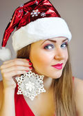 Attractive young woman holding christmas decoration snowflake — Stockfoto