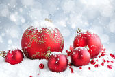 Christmas red balls on snow on festive background — Stock Photo