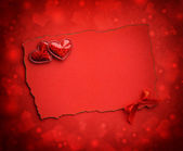 Two decorative hearts are on the sheet of red paper on a red fes — Foto Stock