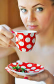 Beautiful woman holds the cup of cowberry tea — Stock Photo