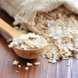 Oat flakes in wooden spoon on wooden background — Stock Photo