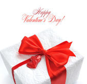 Gift with red satin bow and two hearts on white — Stock Photo