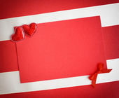 Two decorative hearts are on the sheet of red paper — 图库照片