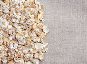 Oat flakes on linen tablecloth — Stock Photo