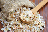 Oat flakes on wooden table — Stock Photo