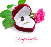 Red velvet box with golden ring and pink rose on a white background — Stock Photo