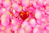 Decorative hearts on a pink rose petals, romantic background — Stock Photo