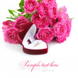 Red velvet box with golden ring and bouquet of pink roses on a white background — Stock Photo #40625587