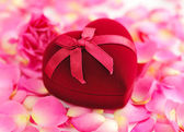 Heart-shaped Gift Box on rose petals — Stock Photo