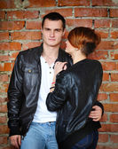 Young enamoured pair on background of red brick wall — ストック写真