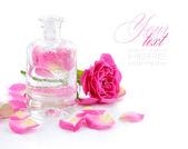 Láhev silice a růžové růže izolovaných na bílém — Stock fotografie