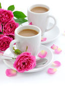 Two cups of coffee and pink roses on white background — Stock Photo