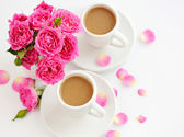 Two cups of coffee and pink roses on white background — Stockfoto