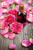 Essential oil with rose petals on wooden background — Stock Photo