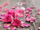 Essential oil with rose petals on wooden background — Fotografia Stock