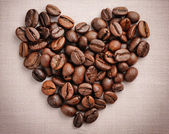 Heart from coffee beans on a linen cloth — Stock Photo