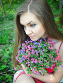 Beautiful young woman with the bouquet of spring flowers — Stockfoto