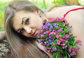 Beautiful young woman with the bouquet of spring flowers — Stock Photo