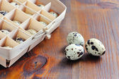Quail eggs in wooden box, packaging, tray on wooden background — Stock Photo
