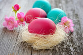 Colorful easter eggs on old wooden table — Stock Photo