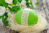 Easter green egg is in a nest on a old wooden background — Stock Photo