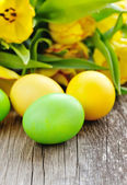 Easter eggs with tulips on old wooden table — Stockfoto