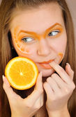 Young beautiful woman with creative orange makeup with orange in her hand — Stock Photo