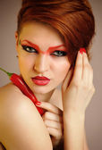 Portrait of beautiful woman with creative red makeup keeps chili peppers — Stock fotografie