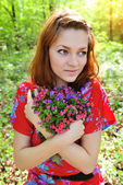 Beautiful young woman with the bouquet of spring flowers — Foto Stock