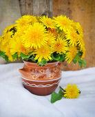 Bouquet of dandelions in a ceramic jug — Stock Photo